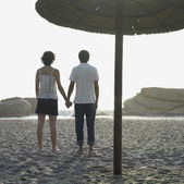 Young couple holding hands underneath umbrella on beach — Foto de Stock