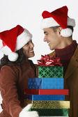 Jeune couple portant des chapeaux de santa avec cadeaux — Photo