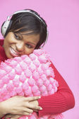 Woman with pillow wearing headphones — Stock Photo