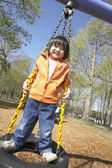 Asian child standing on tire swing — Stock Photo