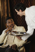 Waiter bringing African man a drink — Stock Photo