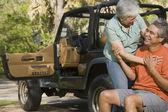 Senior Hispanic couple hugging next to jeep — Stock Photo