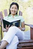 Retrato de mujer sentada en la cubierta por el lago leyendo libro — Foto de Stock