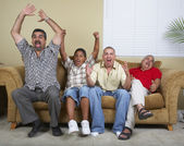 Multi-generational Hispanic male family members cheering on sofa — Stock Photo
