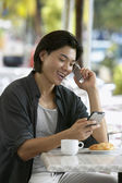 Young man talking on cell phone at breakfast table — Stock Photo