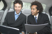 Two businessmen working in backseat — Stock Photo