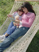 Mother and daughter reading in a hammock — Stock Photo