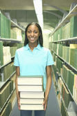 Young woman carrying heavy stack of books — Stock Photo