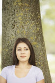 Hispanic woman leaning against tree — Stock Photo