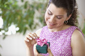 Woman smiling and opening gift — Stock Photo