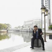 Biznesmen rozmowy na telefon komórkowy przez rzekę — Zdjęcie stockowe