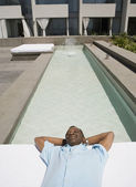 Senior African man laying next to swimming pool — Foto Stock