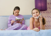 Hispanic sisters reading and using cell phone on bed — Stock Photo