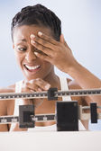 African American woman weighing self — Stock Photo