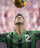 Soccer player heading the ball — Stock Photo