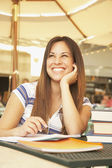 Hispanic woman at cafe table with school books — Stock Photo
