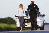 Policeman watching young woman walk in a straight line — Stock Photo