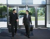 Businessmen entering building — Stock Photo