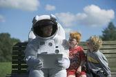 Astronaut talking to children — Stock Photo