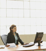 Businesswoman typing on computer at desk — Stock Photo
