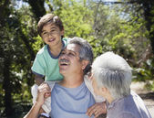 Hispanic grandparents with grandson outdoors — Stock Photo