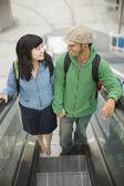 Young couple riding escalator — Stock Photo