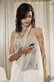 Fashionably dress Hispanic woman looking at cell phone — Stock Photo