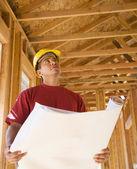 Trabajador de la construcción masculina con planos en construcción — Foto de Stock