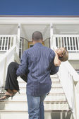 Rear view of man carrying woman up stairs — Stock Photo