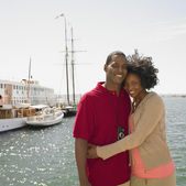 African couple hugging next to water — Stock Photo