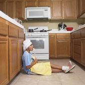 Niño hispano lamiendo cuchara de madera en cocina — Foto de Stock