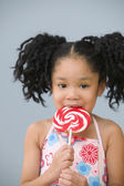 Portrait of Asian girl with ponytails eating sucker — Stock Photo