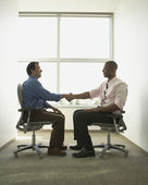 Businessmen shaking hands in swivel chairs — Stock Photo