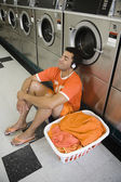 Man sitting on floor listening to music in laundromat — Stock Photo