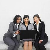 Multi-ethnic businesswoman looking at laptop — Stock Photo