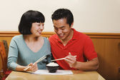 Asian couple eating rice — Stock Photo