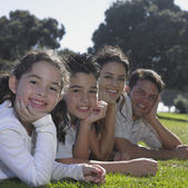 Family posing for the camera on green lawn — Stock Photo