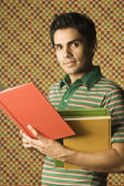 Young man holding multicolored books — Stock Photo