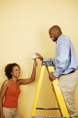 Couple with light bulb on ladder — Stock Photo