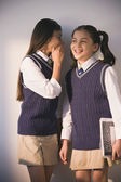 Two school girls in uniform whispering — Stock Photo