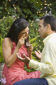 Hispanic woman appraising engagement ring in front of man — Stock Photo
