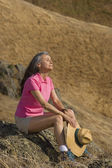 Senior woman resting on rocky area outdoors — Stock Photo