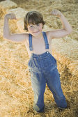Young boy wearing overalls and flexing muscles in hay — Stock Photo