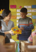 Female teacher helping student to tell time — Stock Photo
