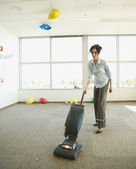 Businesswoman vacuuming after office party — Stock Photo