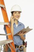 Hispanic female construction worker talking on cell phone — Stock Photo