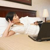 Asiatische geschäftsfrau vor dem Fernseher im hotel — Stockfoto