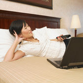 Asian businesswoman watching television in hotel — Stock Photo