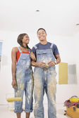 Portrait of couple in overalls painting — Stock Photo