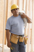 Construction worker carrying wiring on shoulder — Stock Photo